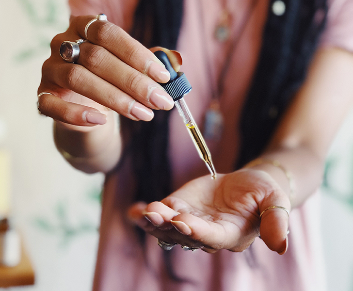 A woman applying ointment to the palm of her hand using a dropper