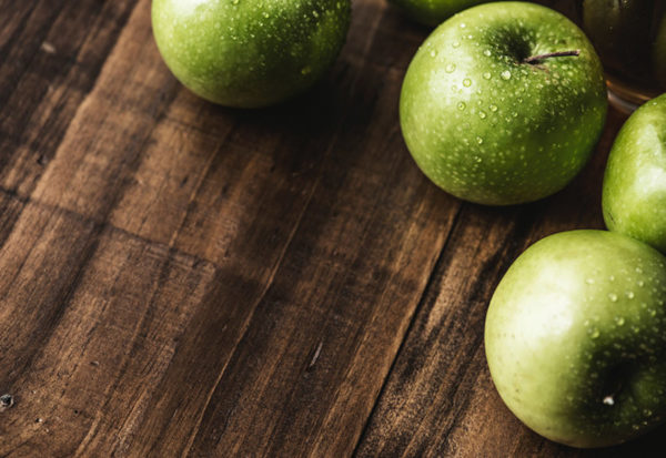 Green Granny Smith apple varieties sitting on a wood surface