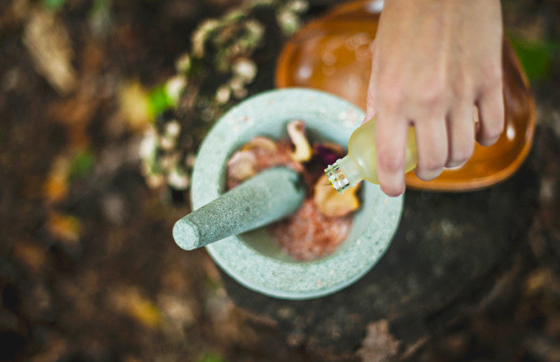 Hand pouring liquid into a mortar to be pounded with herbs