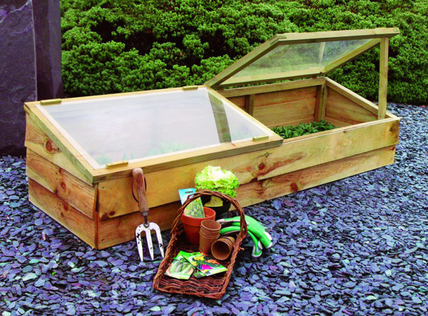 A cold frame box with garden supplies sitting next to it