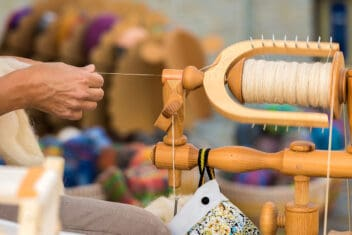 Person spinning wool into yarn on a spinning wheel